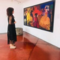 Patricia Tapia López-Voß vor einem Bild von Elmer René Rojas (Akryl auf Stoff) im Hotel Museo Casa Santo Domingo, Antigua Guatemala